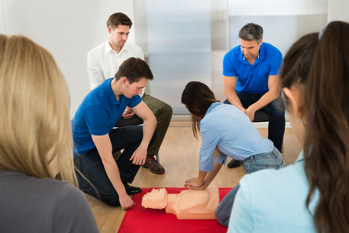 Instructor Demonstrating CPR Chest Compression On A Dummy, onsite training, group training on clients site, private courses